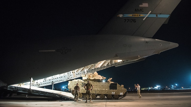 U.S. Airmen assigned to the 386th Expeditionary Logistics Readiness Squadron help guide a U.S. Army Soldier loading an M2 Bradley Fighting Vehicle onto a U.S. Air Force C-17 Globemaster III at Ali Al Salem Air Base, Kuwait, Oct. 30, 2019. Airmen and Soldiers coordinated efforts to transport the BFV within the U.S. Central Command theater of operations to assist in ongoing efforts within the region. (U.S. Air Force photo by Capt. Thomas Barger)