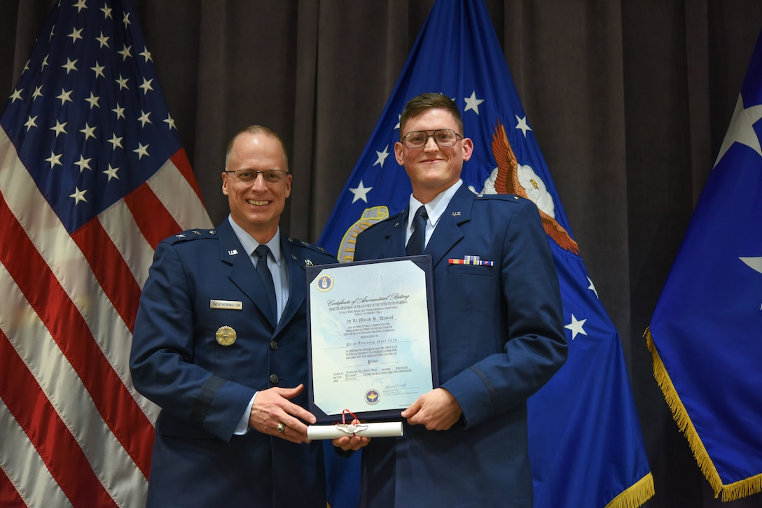 """Maj. Gen. Mark Weatherington, Air Education and Training Command deputy commander, presents 2nd Lt. Micah Daniel with his pilot's wings during a dual commissioning and """"winging"""" ceremony Dec. 19, 2019, at Maxwell Air Force Base, Alabama. Daniel made history as one of the first prior-enlisted Airmen to receive pilot's wings at the same time as his lieutenant's bars. (U.S. Air Force photo by Staff Sgt. Quay Drawdy)"""