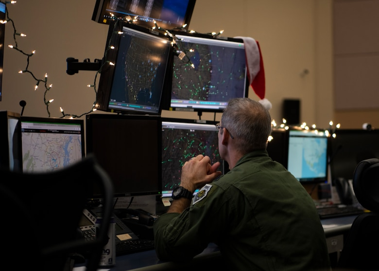 Lt. Col. Justin Podnar, 601st Air Operations Center senior air defense officer, tracks flight patterns of military aircraft to ensure Santa has a safe route for his deliveries, Tyndall Air Force Base, Florida, Dec. 23, 2019. North American Aerospace Defense Command uses their satellite technology to provide real time updates on Santa's location across the world. (U.S. Air Force photo by Senior Airman Cheyenne Larkin)