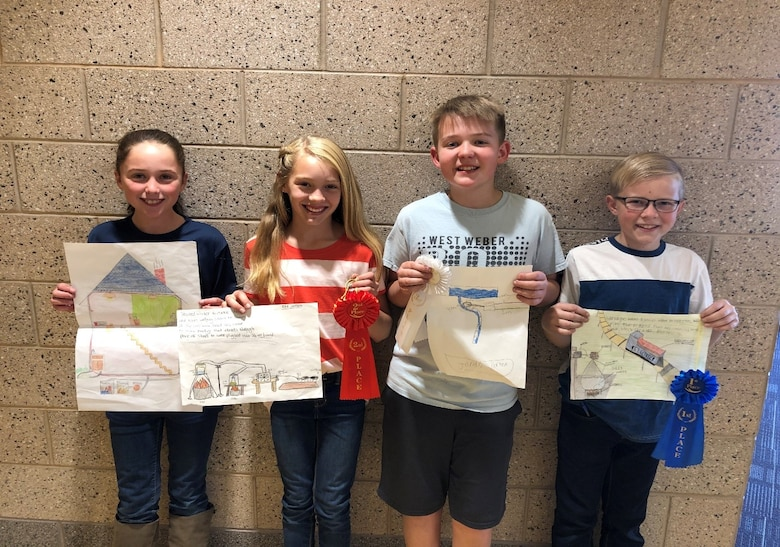 Four 6th graders from est Weber Elementary hold up their winning Energy Action Month Art Contest drawings.
