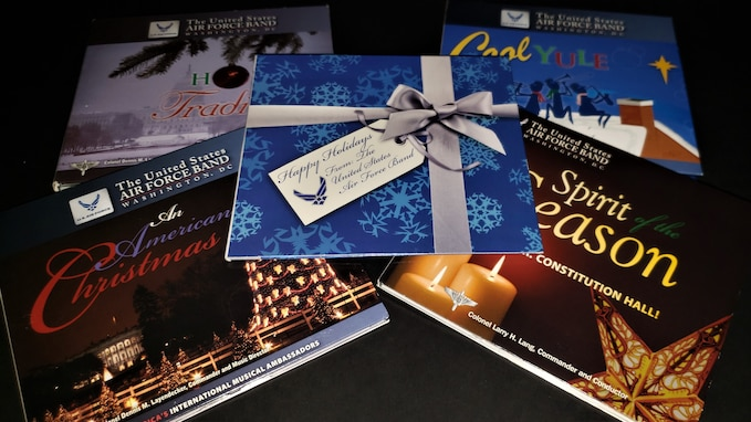 Picture of five compact disc cases for various holiday recordings by The U.S. Air Force Band in Washington, D.C. The cover for each album features holiday graphics and imagery such as Christmas trees and snowflakes.