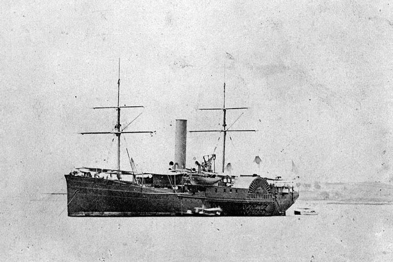 A 1860s-era side-wheel steamship with two masts sits in water offshore.