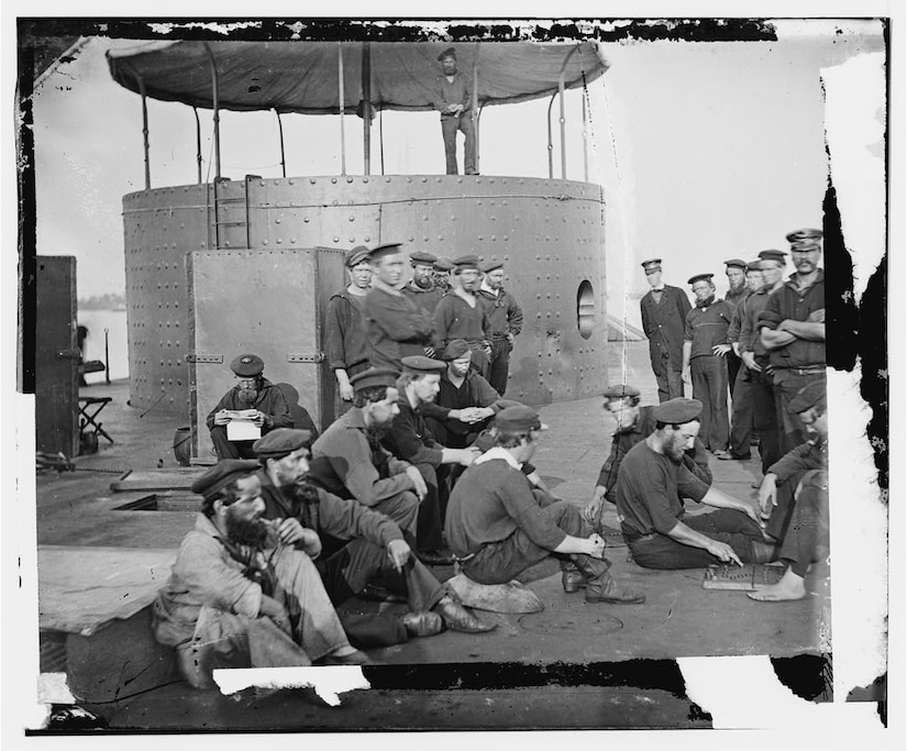 Several Civil War-era sailors sit on the deck of an ironclad warship. A large, round turret is nearby.