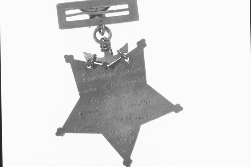 The backside of a Medal of Honor attached to a clasp. Illegible engraving is on the medal.