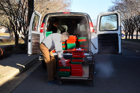 """George Irby, chief executive officer of the Happy Irby Fund, and Bruce Hanson, member of the Happy Irby Fund Board, place the finished wrapped gifts in a van to be transported to schools Dec. 19, 2019, on Columbus Air Force Base, Miss. The program was founded by the late George """"Happy"""" Irby, long-term staff member at the Columbus Club in the 1950s and is continued by his son, George Irby. (U.S. Air Force photo by Airman 1st Class Jake Jacobsen)"""