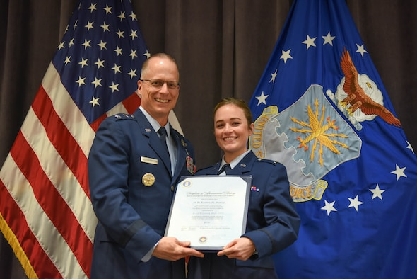 """Maj. Gen. Mark Weatherington, Air Education and Training Command deputy commander, presents 2nd Lt. Kristen Savage with her pilot's wings during a dual commissioning and """"winging"""" ceremony Dec. 19, 2019, at Maxwell Air Force Base, Alabama. Savage was a student pilot who graduated PTN version 2, an Air Education and Training Command program to explore what is possible in training with the use of innovative technology and how it can be applied to not only pilot training but also to training across AETC.  She earned her wings, but couldn't wear them until she commissioned. (U.S. Air Force photo by Staff Sgt. Quay Drawdy)"""