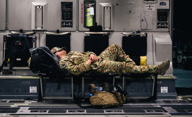 A U.S. Air Force Airman sleeps inside a C-17 Globemaster III during a flight over an undisclosed location in support of Operation Freedom Sentinel, Jan. 22, 2018. Airmen supporting OFS work to prevent Afghanistan from becoming a safe haven for al Qaeda and international extremist groups. (U.S. Air Force illustration)