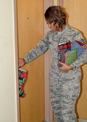 U.S. Air Force Technical Sgt. Chelsea Steel, 8th Civil Engineer Squadron Airman dorm leader, places a stocking full of candy and gifts on a dorm resident's door handle at Kunsan Air Base, Republic of Korea, Dec. 11, 2019. The ADL's placed stockings on over 500 doors in the building while many residents were at work. (U.S. Air Force photo by Tech. Sgt. Joshua Arends)