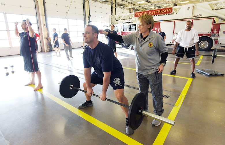 Peer Fitness trainer Sue Shepherd, right, works with Andy Short, 788th Civil Engineer Squadron firefighter, at Wright-Patterson Air Force Base, Ohio on Thursday, December 19, 2019. Firefighters from Wright-Patt, the 72nd Air Base Wing Civil Engineer Squadron, Tinker AFB, Oklahoma and 66th Civil Engineer Squadron Hanscom AFB, Massachusetts, joined in the training which is aiming to double the number of certified peer trainers at fire stations. (U.S. Air Force Photo by Ty Greenlees)