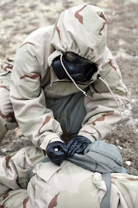 A Soldier wearing Mission Oriented Protective Posture, or MOPP, protective gear simulates using a CBD auto-injector device on a casualty during a field test  at Joint Base San Antonio-Camp Bullis