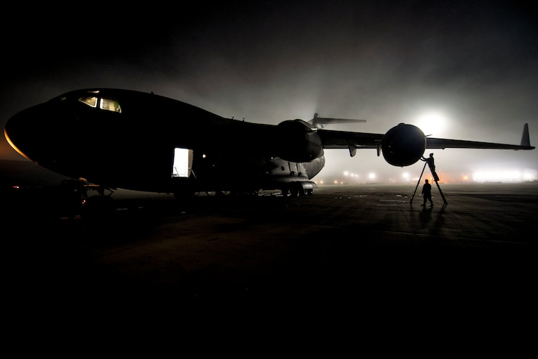 An airman on a ladder, shown in silhouette, inspects an aircraft engine on a dark flightline.