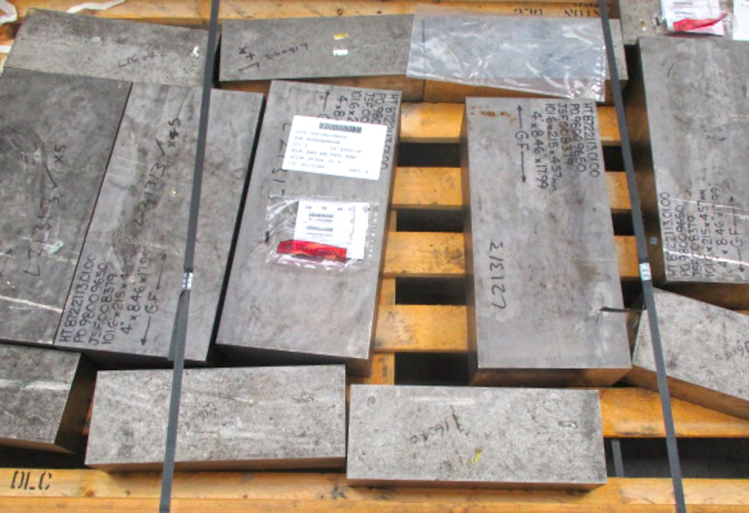 Various-sized bars of titanium sit on a pallet awaiting shipment.