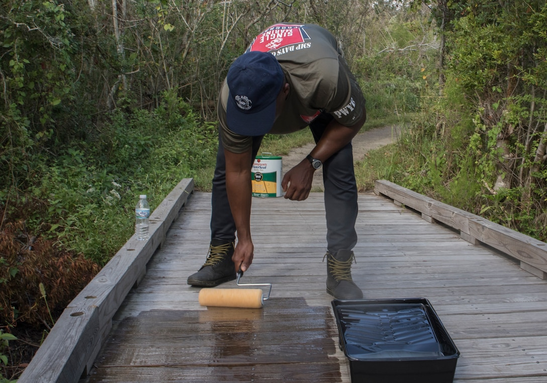 A U.S. Marine applies a waterproofing solution to a wooden bridge during a Single Marine Program volunteer event at Fort Macon State Park, N.C., Sept. 2.