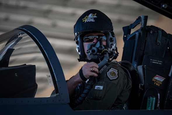 A pilot adjusts his oxygen mask in the cockpit of an F-15E Strike-Eagle fighter jet.