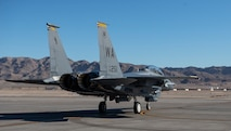 An F-15E Strike Eagle fighter jet taxis on the flight line.