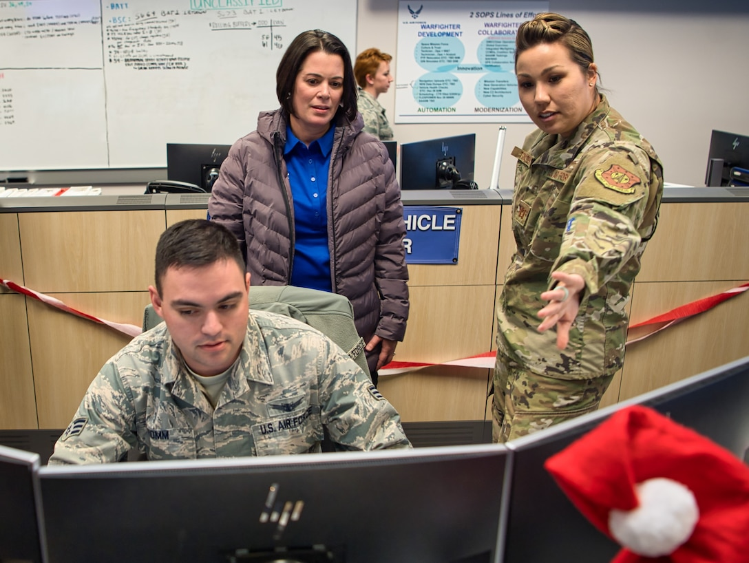 Capt.  Angela Tomasek, 2nd Space Operations Squadron engineering flight commander, briefs retired Col. Nicole Malachowski, while Senior Airman Sean Romm, 2nd SOPS space systems operator, mans a control station, while on a tour of the 2nd SOPS floor during her visit to Schriever Air Force Base, Colorado, Dec. 19, 2019. Malachowski, the first female Thunderbird pilot, spent 21 years in the Air Force. After being medically discharged due to a life threatening tick borne illness in 2017, Malachowski decided to use the pain and lessons learned to bring hope to thousands through her motivational speeches focused on the value and importance of resilience, resurgence and re-invention. (U.S. Air Force photo by Katie Calvert)