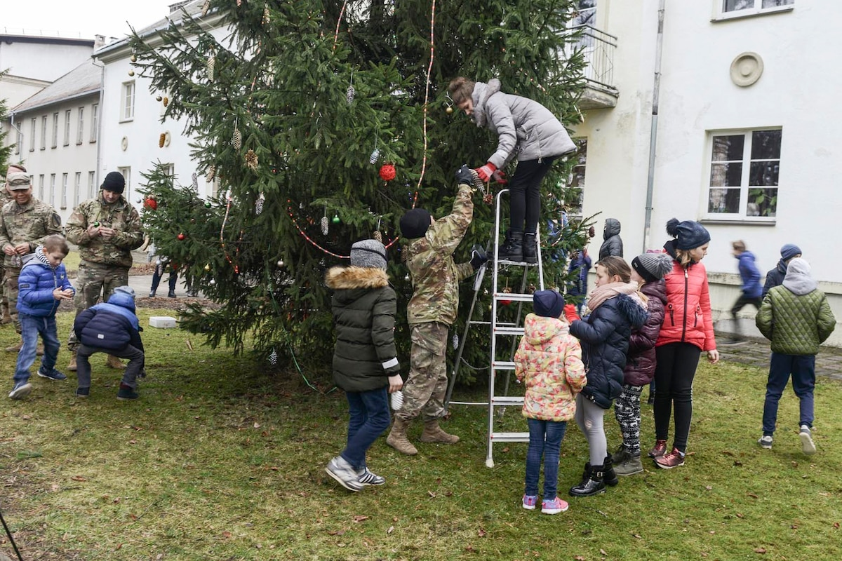Soldiers and children decorate a Christmas tree outside a white building.