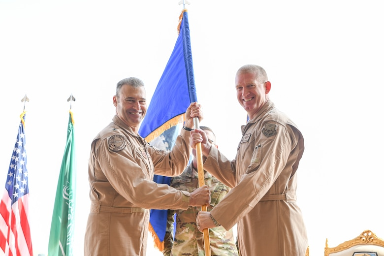 Prince Sultan Air Base, Kingdom of Saudi Arabia -- U.S. Air Force Lt. Gen. Joseph Guastella, Air Forces Central Command commander, presents Brig. Gen. John C. Walker, former deputy commander of the 9th Air and Space Expeditionary Task Force in Afghanistan, the guidon during the 378th Air Expeditionary Wing activation ceremony here, Dec. 17, 2019.