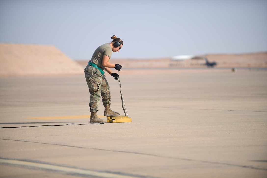 U.S. Air Force Senior Airman Eleanor Lapi, 555th Expeditionary Aircraft Maintenance Unit weapons load crew member, prepares aircraft wheel chocks for the arrival of an F-16 Fighting Falcon, assigned to the 555th Expeditionary Fighter Squadron, Dec. 2, 2019 at Prince Sultan Air Base, Saudi Arabia.