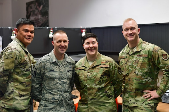 U.S. Air Force Senior Master Sgt. Arturo Quinones, 786th Civil Engineer Squadron facilities superintendent, left, Master Sgt. Justin Jones, 786th CES requirements and optimization section chief, Senior Airman Ariana M. Ingalls, 786th CES pavement and equipment journeyman, and Staff Sgt. Joshua Burch, 786th CES data analytics NCO in charge, pose for a photo during a gathering of leadership and peers to recognize Ingalls as Airlifter of the Week at Ramstein Air Base, Germany, Dec. 19, 2019. Ingalls coordinated the building and operation of a haunted house during Fall 2019, that raised $4,800 for scholarships given to Kaiserslautern Military Community high school seniors and $750 for the CES Booster Club. (U.S. Air Force photo by Airman 1st Class John R. Wright)