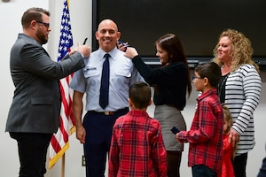 Lt. Col. Frank Mercurio, 911th Logistics Readiness Squadron commander, smiles as family members pin on his new rank during a dual promotion and assumption of command ceremony at the Pittsburgh International Airport Air Reserve Station, Pennsylvania, Dec. 7, 2019.