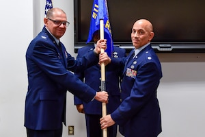 Lt. Col. Frank Mercurio, right, accepts the 911th Logistics Readiness Squadron guidon from 911th Mission Support Group Commander Col. Kenneth Lute during an assumption of command ceremony at the Pittsburgh International Airport Air Reserve Station, Pa., Dec. 7, 2019.