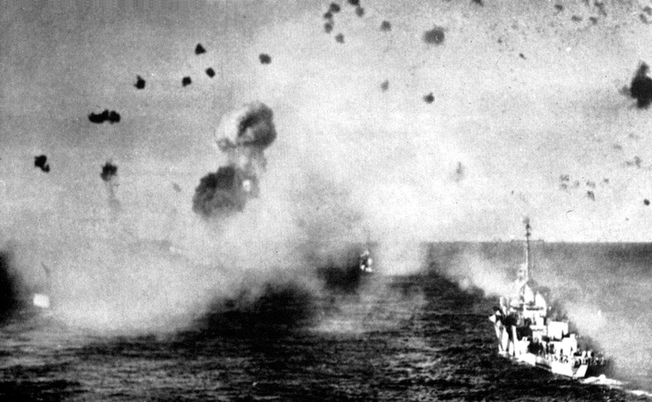 Ships under attack with debris and smoke in the air in a black and white photo.
