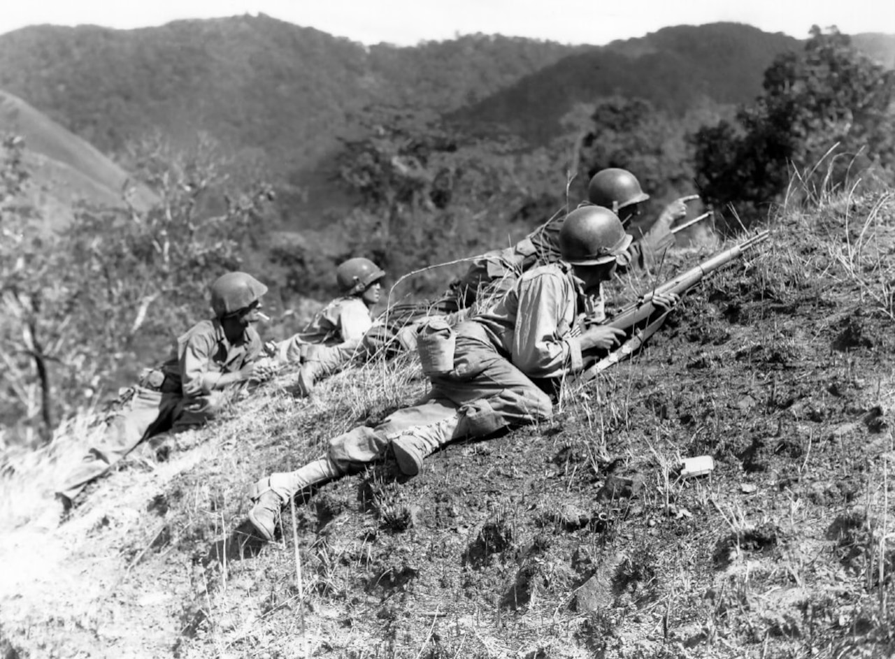 Soldiers crawl up a hill with mountains in the background.