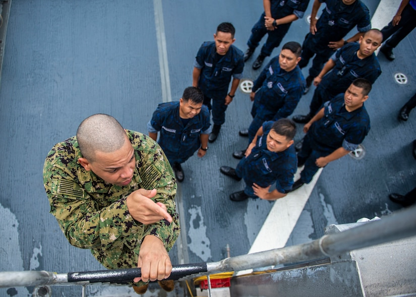 A sailor in camouflage climbs a ladder while sailors in blue uniforms watch from the deck below.