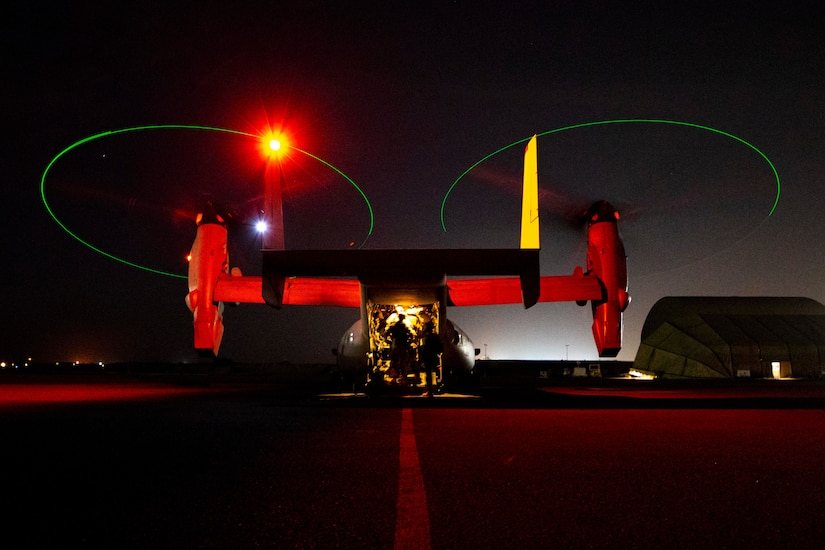 Marines are illuminated inside an open aircraft on a dark flightline.