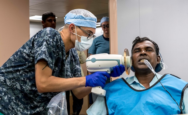 Hospital Corpsman Angel Vega takes an X-ray of a patient's mouth aboard USNS Mercy during Pacific Partnership 2018.