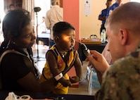 Lt. Cmdr. Scott Williams examines a child's eyes during Pacific Partnership 2018.
