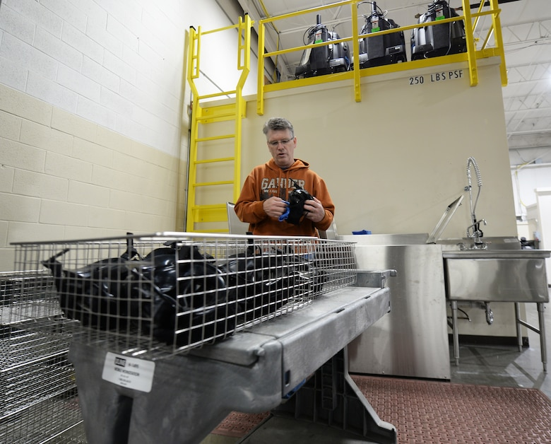 Tom Weise, 375th Logistic Readiness Squadron individual protective equipment specialist, places M50 gas masks in metal baskets before putting them in the gas mask dryer, Jan. 28, 2019, at Scott Air Force Base, Illinois. The dryer allows the gas masks to be put back out for distribution quicker than if they were air dried. This enables more Airmen to be able to get equipment all at once.