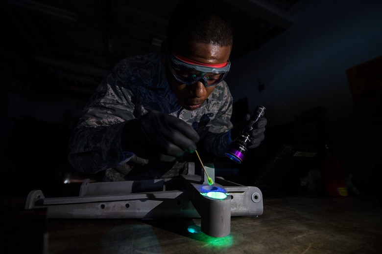 An Airman inspects a piece of equipment with a black light