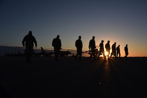 Airmen walk the flightline looking for debris
