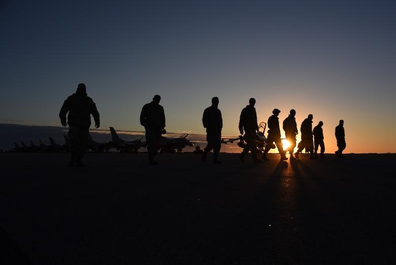 Airmen walk the flightline looking for debris
