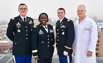 Three Army soldiers stand to the left of a civilian doctor on a rooftop overlooking Camden, N.J.