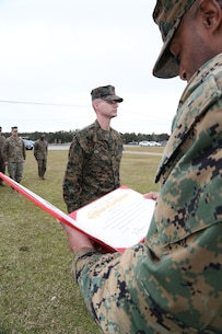 Sgt. James W. Wade II, administrative noncommissioned officer, Headquarters Company, Marine Corps Logistics Command, stands at attention while Master Sgt. Corey Moore, career planner, MARCORLOGCOM, reads the Certificate of Reenlistment aboard Marine Corps Logistics Base Albany, Ga., Jan. 30.