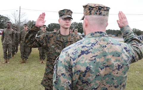 Sgt. James W. Wade II, center, administrative noncommissioned officer, Headquarters Company, Marine Corps Logistics Command, recites the Oath of Enlistment from Maj. Ryan C. Fielding, company commander, Headquarters Company, MARCORLOGCOM, during a ceremony aboard Marine Corps Logistics Base Albany, Ga., Jan. 30.