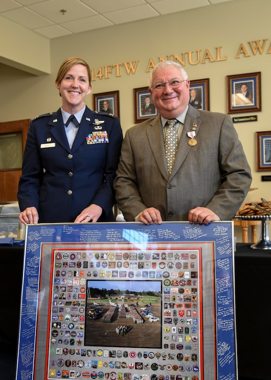 """Col. Samantha Weeks, 14th Flying Training Wing commander, hands Richard """"Sonic"""" Johnson, former 14th FTW Public Affairs chief, a retirement memento during his retirement reception Jan. 25, 2019, on Columbus AFB, Mississippi. The photo was surrounded by almost all of the student patches from Specialized Undergraduate Pilot Training classes since he was the public affairs chief at Columbus AFB. (U.S. Air Force photo by Melissa Doublin)"""