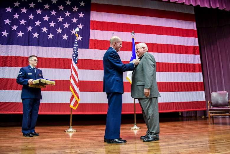 """Air Force Vice Chief of Staff Gen. Stephen Wilson pins the Outstanding Civilian Career Service Award onto Richard """"Sonic"""" Johnson, former 14th Flying Training Wing Public Affairs chief, during Johnson's retirement ceremony at the Kaye Auditorium Jan. 25, 2019, on Columbus Air Force Base, Mississippi. Wilson officiated the retirement ceremony. (U.S. Air Force photo by Melissa Doublin)"""