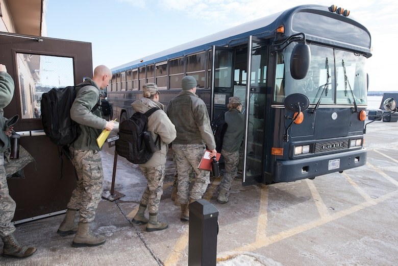Offutt Airmen board a bus after processing through an exercise deployment line of the Installation Deployment Readiness Cell at Offutt Air Force Base, Nebraska Jan. 29, 2019. The members participated in Phase I of Operational Readiness Exercise Winter Havoc that tested Offutt's ability to process and deploy a large amount of personnel and equipment on short notice. (U.S. Air Force photo by Delanie Stafford)