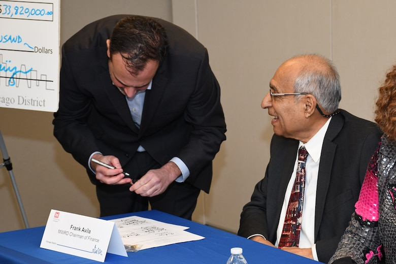 Commissioner Marcelino Garcia (standing) of the Metropolitan Water Reclamation District of Greater Chicago, signs a ceremonial copy of the project partnership agreement between the Corps and MWRD Jan. 31 while MWRD Commissioner of Finance Frank Avila looks on. The MWRD received $33.8 million in federal funds under authority of Section 1043 of the Water Resources Reform and Development Act of 2014, which allows federal funds to transfer through the U.S. Army Corps of Engineers to local sponsors for authorized projects. (U.S. Army photo by Patrick Bray/Released)