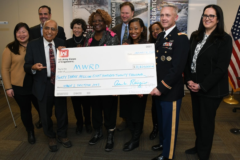 The board of commissioners for the Metropolitan Water Reclamation District of Greater Chicago, hold a novelty check for $33.8 million with Col. Aaron Reisinger (front row, right), commander and district engineer of the U.S. Army Corps of Engineers Chicago District, following a signing ceremony Jan. 3. The MWRD received $33.8 million in federal funds under authority of Section 1043 of the Water Resources Reform and Development Act of 2014, which allows federal funds to transfer through the U.S. Army Corps of Engineers to local sponsors for authorized projects. (U.S. Army photo by Patrick Bray/Released)