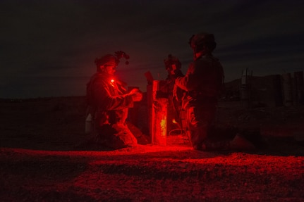 Three Soldiers from the 391st MAC prep an inert crater charge for deployment.
