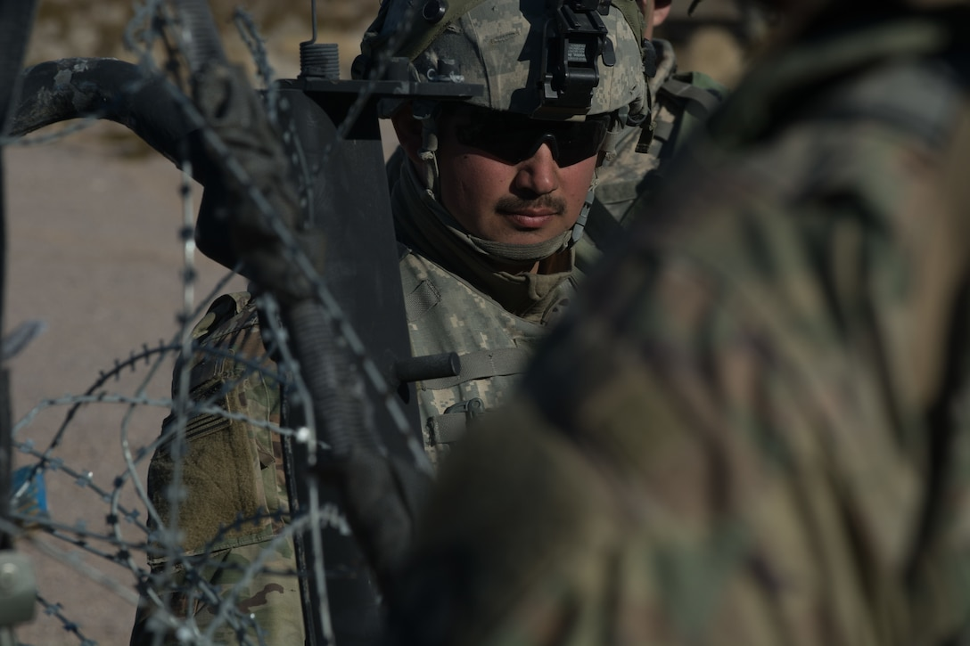 A soldier from the 391st MAC separates pickets, barbed wire and concertina wire before 3rd platoon builds a frag fence.