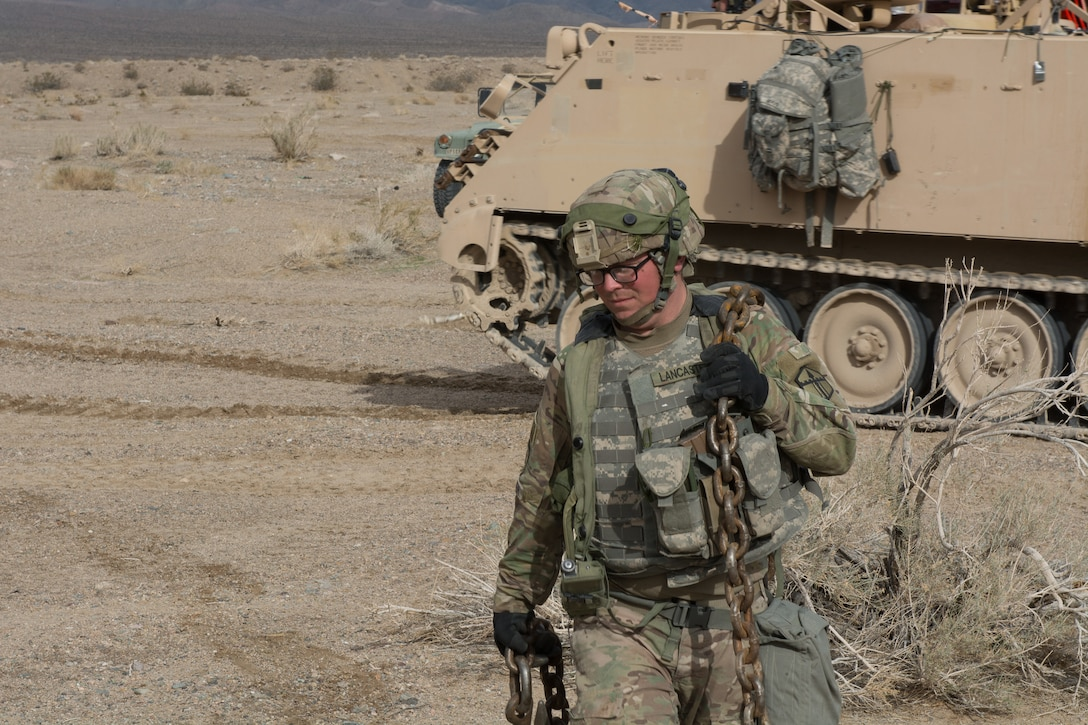 A Soldier from the 391st MAC drags a chain to a disabled vehicle for recovery operations.