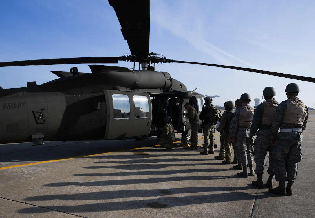 Long shadows are cast upon the flight line as members of the 137th Special Operations Wing, Oklahoma Air National Guard, line up to board an Oklahoma Army National Guard UH-60M Black Hawk at Tinker Air Force Base during SENTRY REX 19-01 exercise on Jan. 15th.