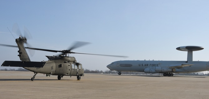 An Oklahoma Army National Guard UH-60M Black Hawk helicopter with rotors turning awaits the take-off of an Air Force E-3 Sentry during a SENTRY REX 19-01 exercise period Jan. 15, Tinker Air Force Base.