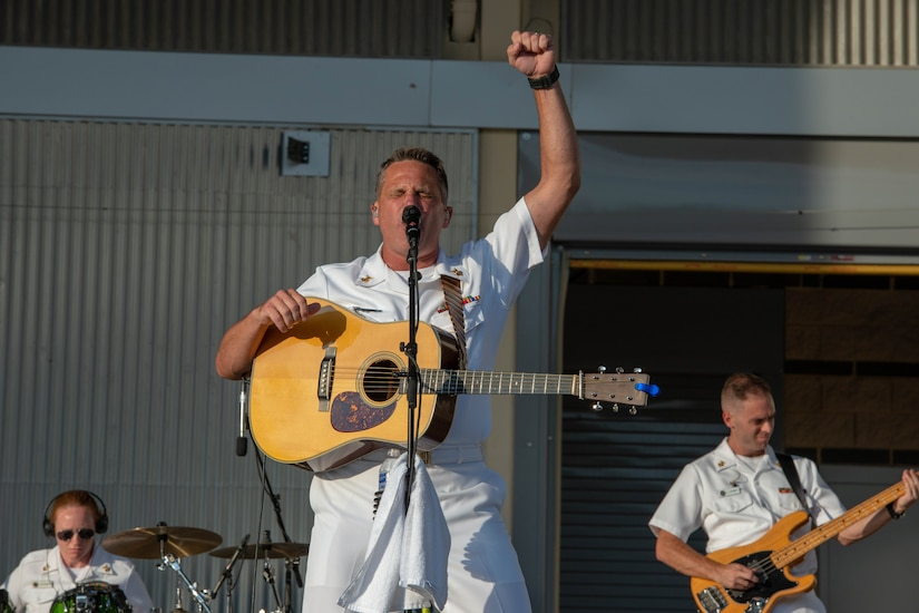 Navy guitarist pumps his fist in the air.
